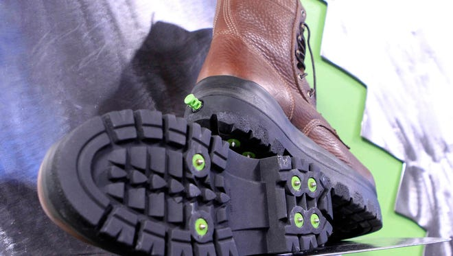 In this Thursday, Nov. 10, 2016 photo, a display shows the bottom and back of boots at the KickSpike store in Anchorage, Alaska. Activate the green button on the back of the boot heel and 7mm steel cleats pop out. Kick the button again and the cleats retract, allowing the wearer to walk inside without tearing up floors. The boots are a new option for walking safely in Anchorage, where ice can be found on streets up to seven months per year.
