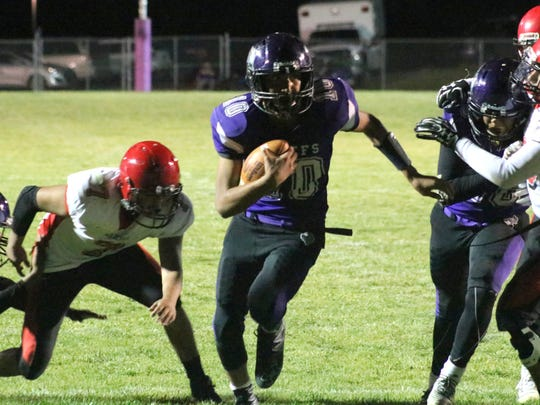 Mescalero's Aloysius Comanche, center, runs through a hole during a game against Springer on Sept. 15 at Chiefs Stadium.