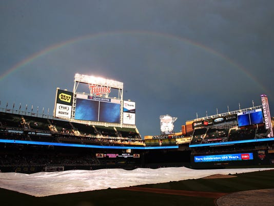 A rainbow signals the end of a rain delay as grounds crew members remove the tarp before the Minnesota Twins against the Cleveland Indians baseball game, Saturday, Sept. 20, 2014, in Minneapolis. (AP Photo/Jim Mone)