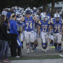 Bommbers Austin Gamblin, from left, Drew Strope and Jason Elizondo lead the team onto the field.