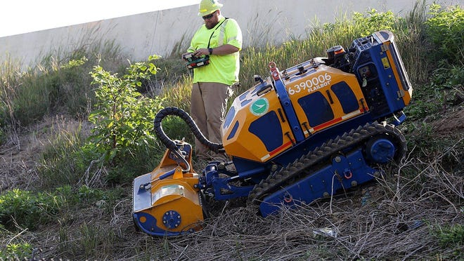 Jamason Rohaley, a highway technician for the Ohio Department of Transportation, controls the Bomford Flailbot mower on a ramp bank off Interstate 77 in Canton.