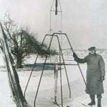 Robert H. Goddard is shown standing with the world's first liquid-propelled rocket in Auburn, Mass., on March 16, 1926. When launched, the rocket soared 41 feet high and carried 184 feet in 2  1/2 seconds. It moved at 60 miles per hour.