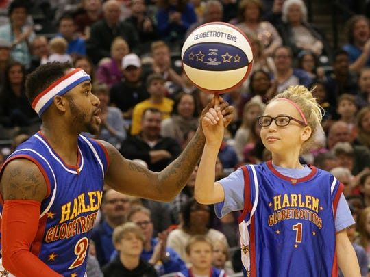 Harlem Globetrotter Dizzy, helps Neve Nash spin the ball during a competition, Jan. 14, 2017. The Harlem Globetrotters took on the World All-Stars at Bankers Life Fieldhouse in Indianapolis.