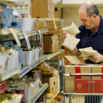 Volunteer Mike Walsh stocked the shelves last January 2015 with bags of long grain rice at the Catholic Charities food shelf.