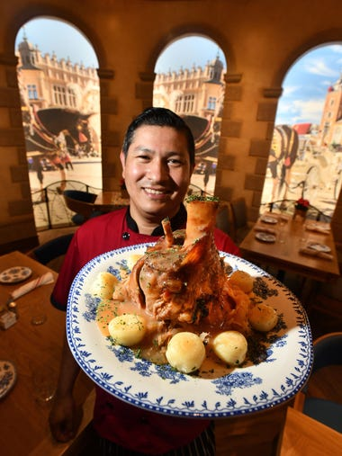 Chef Ramses Romero with a pork shank over sauerkraut