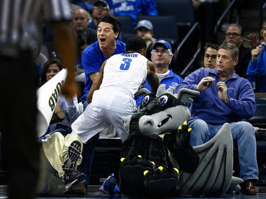 University of Memphis guard Jeremiah Martin  (middle) runs into the crowd while trying to save a loose ball during second half action against UAB at the FedExForum.