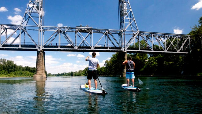 Tod Woodward, left, and Ryan Ross, paddles their stand-up paddleboard on the Willamette River below the Railroad Bridge in Salem.