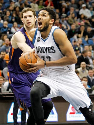 Mar 28, 2016: Minnesota Timberwolves center Karl-Anthony Towns (32) drives to the basket past Phoenix Suns forward Jon Leuer (30) in the first quarter at Target Center.