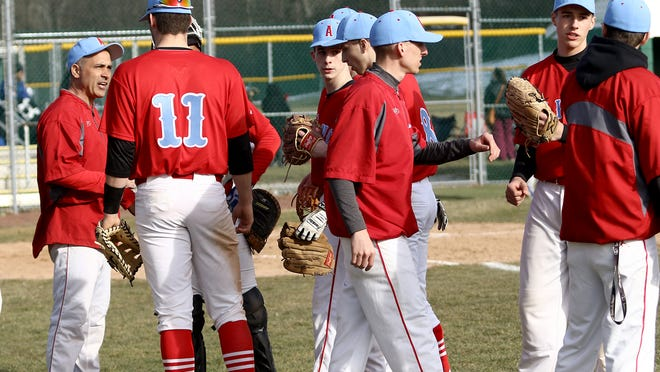 Alliance varsity baseball head coach Jeff Graffice, left, meets with his players between innings during the team's 2018 opener.