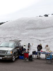 Skiers skiers grill lunch by their vehicle under a