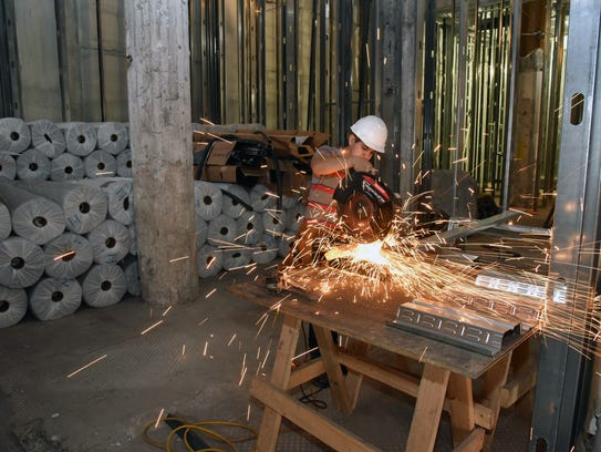 Construction worker Jose Orosco cuts steel framing