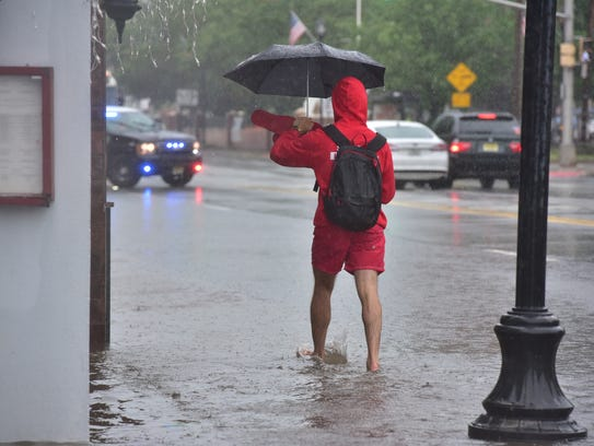 An unidentified man crosses the flooded sidewalk on