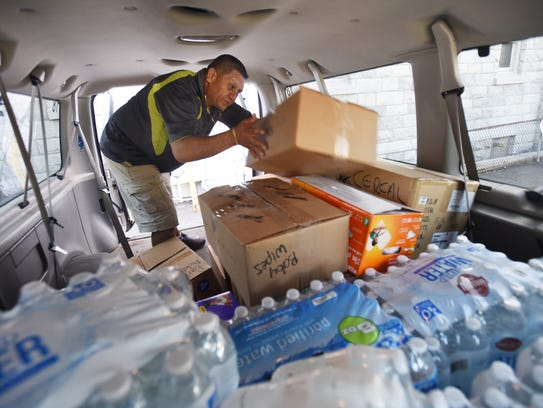 Parishioner Carlos Idrovo sorts donations in a van