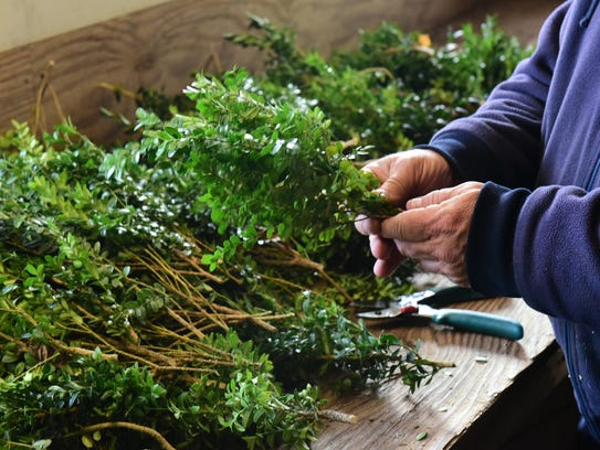 Kenny Perry prepares a 24-inch wreath for a customer Wednesday, Nov. 22, 2017 at Plasterer's Florist, Lincoln Way East, Chambersburg. Asking for clippings from Christmas tree lots and using them to make your own wreaths and other decorations is one of many ways to minimize waste over the holiday season.