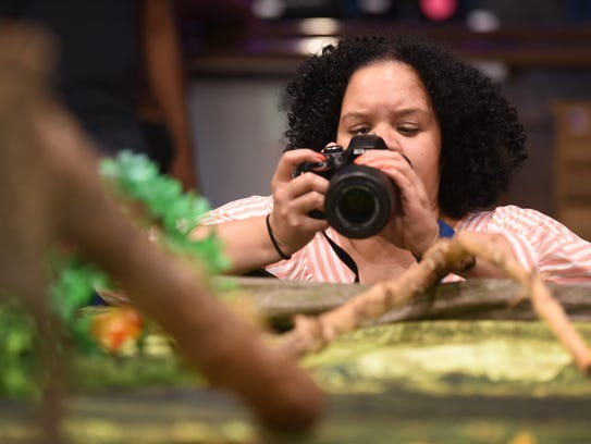 Teaneck Camera Club member Mari Parker checks her images as she photographs a snake at the Wildlife Conservation Center in Garfield on 02/11/18.