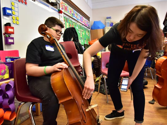 Cello teacher DoYeon Kim, helps Steven Tiburcio, 12,
