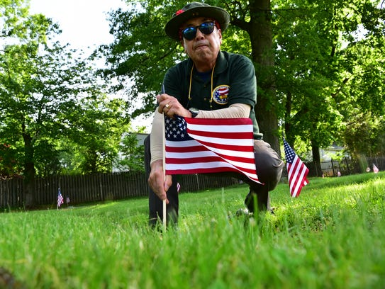 Vietnam Vet James Kim, places a flag on a soldiers
