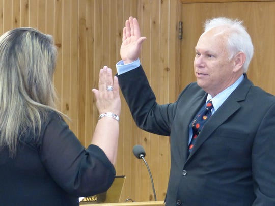 Ruidoso Village Clerk Irma Devine administers the oath to Tim Coughlin, reelected to a second, four-year term.