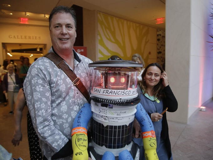 Co-creator David Harris Smith carries hitchBOT, a hitchhiking