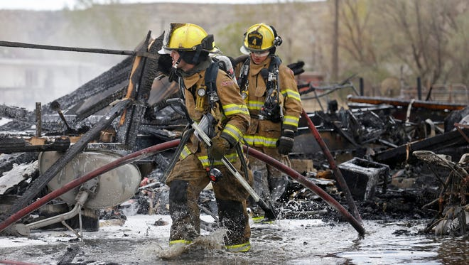 Firefighters with the San Juan County Fire Department extinguish a structure fire on April 23 in Kirtland.