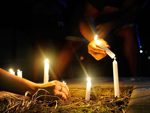 A candlelight vigil is held near the multiple stabbing