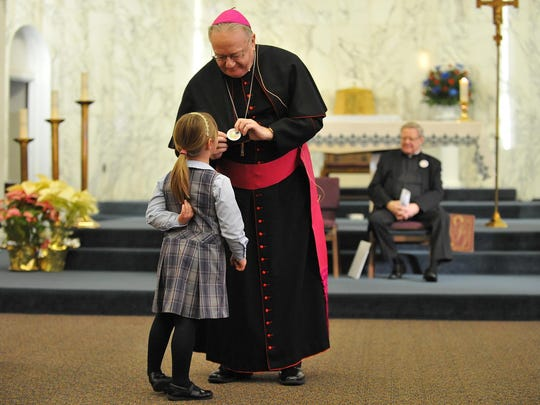 Bishop Schad Regional School first grade student Angelina Felix, 7, reads a pin commemorating Catholic Schools Week worn by Bishop Dennis Sullivan during a prayer service honoring school principal Dr. Patrice DeMartino at Sacred Heart Church, Tuesday, Feb. 2 in Vineland.