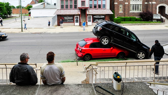 Two men on the steps of the Gethsemane Lutheran Church watch as police and a tow truck respond to a car crash Wednesday afternoon on Church Street. A truck struck a vehicle and lodged it beneath another vehicle.