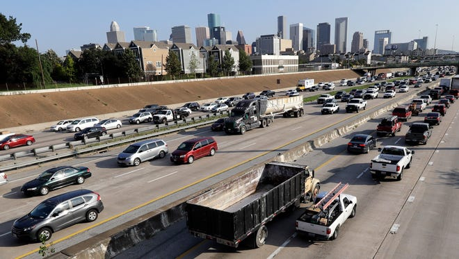 Vehicles travel along the highway near downtown Houston Tuesday, Sept. 5, 2017. Many residents returned to work Tuesday in the aftermath of Hurricane Harvey.