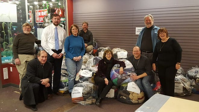Ithaca Rotary Club volunteers sorting clothing for the Share the Warmth project.