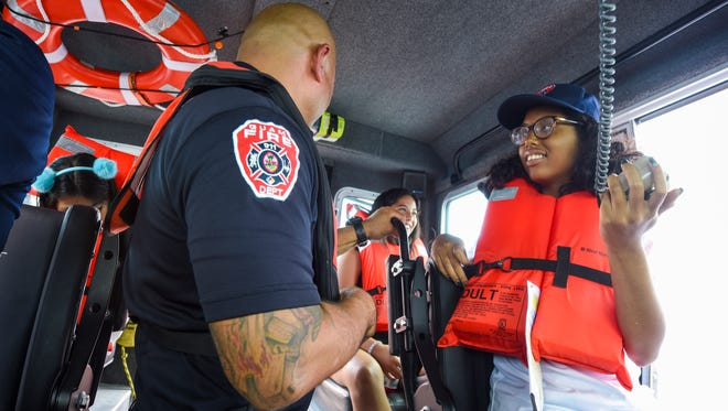 Imani Malanche, right, Guam Fire Department chief of the day, conducts a radio check under the guidance of GFD Battalion Chief Roderick Meno during a short excurison, aboard the agency's Secured Around Floatation Equipped, or SAFE, rescue boat just outside the boat basin in Hagåtña on Wednesday, July 18, 2018. Malanche, a Make-A-Wish recipient from Arizona, is visiting Guam along with other family members, in fulfillment of her wish to see the island and the chance to meet her mother's family. Malanche has been diagnosed with a rare blood disorder.