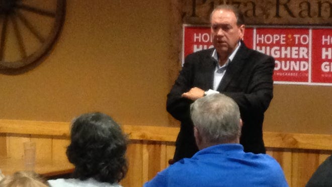 Republican presidential candidate Mike Huckabee talks to about 50 people in Waukee on Wednesday.