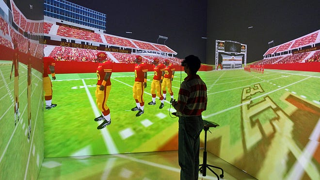 Iowa State Virtual Reality Applications Center scientist Vijay Kalivarapu operates the school's virtual reality application for football recruiting.