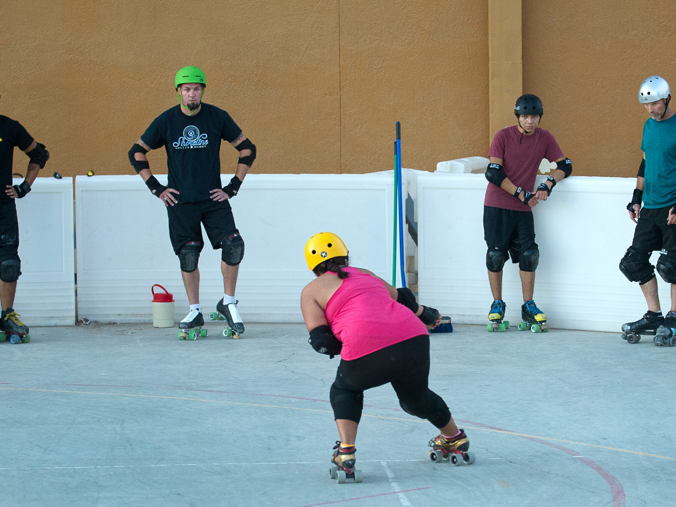Members of the New Mexico Men's Roller Derby Team watch closely as they are taught different types of stops at the rink behind Meerscheidt Recreation Center at a recent practice.