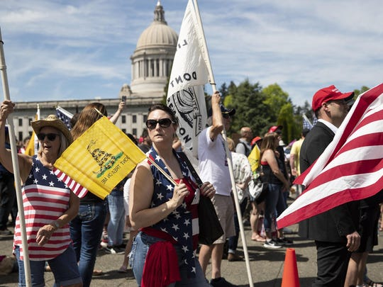 """Parkland, Wash., resident Tammy Snider during a rally against coronavirus restrictions on Saturday at the Washington State Capitol in Olympia, Wash. Snider says she is tired of being at home in quarantine and """"really thinks this is all politics."""""""