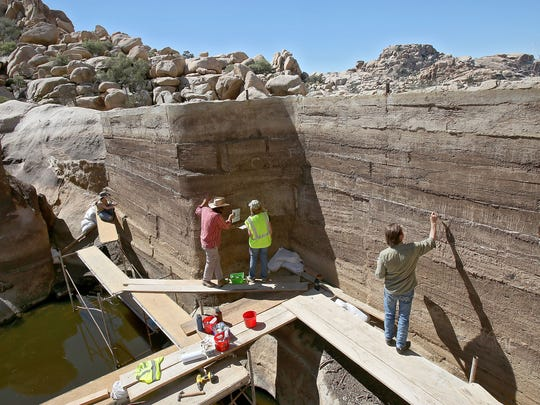 Restoration expters paint over graffiti at the historic Barker Dam in Joshua Tree National Park on Friday, March 27, 2015.