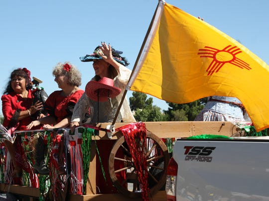 Women wave from atop their float entry in the parade celebrating the Diez y seis de Septiembre fiesta at Mesilla Plaza Saturday.