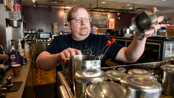 Alan Scherr, owner of Central Perk coffee shop, creates a coffee drink for a customer on April 25, 2018, in St. Cloud. Scherr is under pressure to change the business name due to a trademark held by Warner Bros. Entertainment Inc.