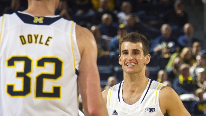 Michigan forward Ricky Doyle (32) congratulates guard Austin Hatch (30) before a free throw attempt in the second half of an NCAA college basketball game against Coppin State at Crisler Center in Ann Arbor, Mich., Monday, Dec. 22, 2014.