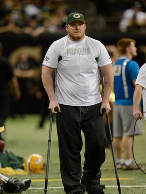 Green Bay Packers guard T.J. Lang uses crutches as he walks the sidelines during Sunday night's game against the New Orleans Saints at the Superdome in New Orleans. Evan Siegle/Press-Gazette Media