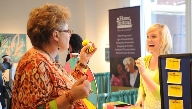 Sue Muetzelburg of Fond du Lac gets a rubber bumblebee from Heidi Vandergrinten at the Fond du Lac Credit Union's booth, at The Reporter's Women's Expo, held at The Thelma Sadoff Center For The Arts in 2014.