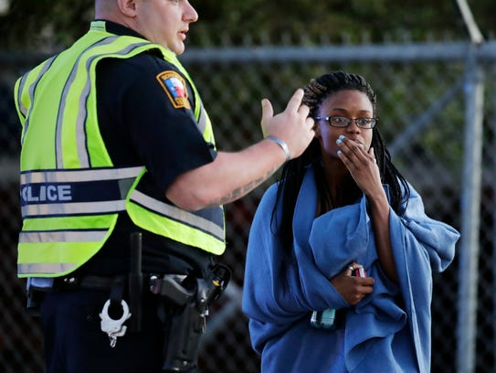 An employee wrapped in a blanket talks to a police