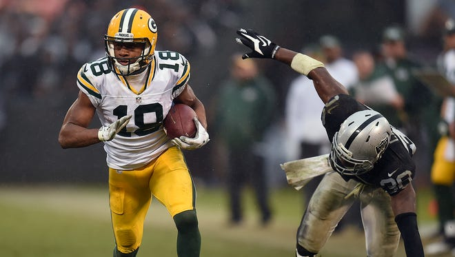 Green Bay Packers receiver Randall Cobb (18) eludes Oakland Raiders cornerback TJ Carrie (38) after making a catch in the fourth quarter at the O.co Coliseum.
