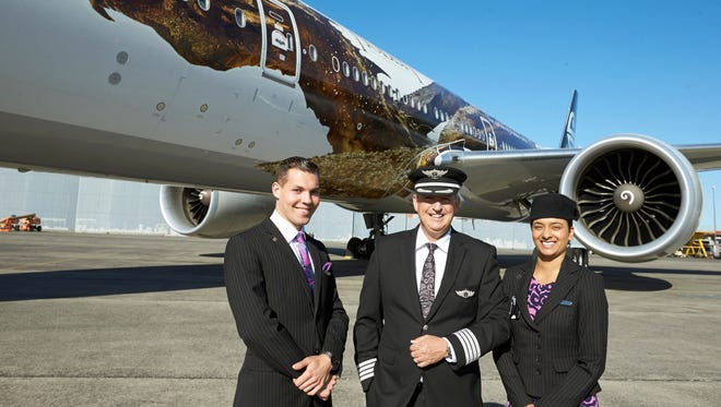 Air New Zealand crew members Maxence Cherri, left, Priyanka Girish, right, and Captain David Morgan stand in front of a plane with an image of the dragon Smaug on Dec. 2, 2013, in Auckland, New Zealand.
