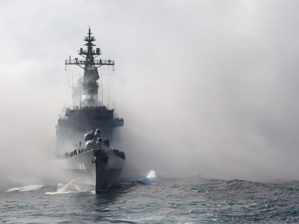 Japan's Maritime Self-Defense Force (MSDF) escort ship Kurama sails through smoke during a fleet review off Sagami Bay, Kanagawa prefecture. Thirty-six MSDF vessels with navy ships from Australia, India, France, South Korea and the United States part