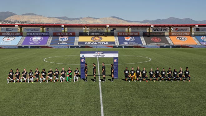 Players for the Portland Thorns, left, and the North Carolina Courage kneel during the national anthem before the start of their NWSL Challenge Cup soccer match at Zions Bank Stadium Saturday, June 27, 2020, in Herriman, Utah.