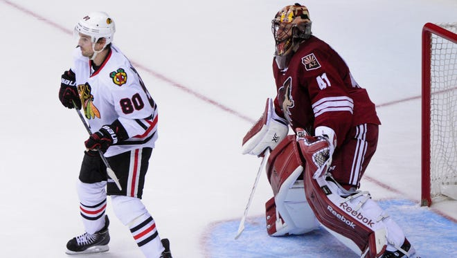 March 12, 2015; Glendale; Arizona Coyotes goalie Mike Smith (41) and Chicago Blackhawks center Antoine Vermette (80) watch the play during the second period at Gila River Arena.