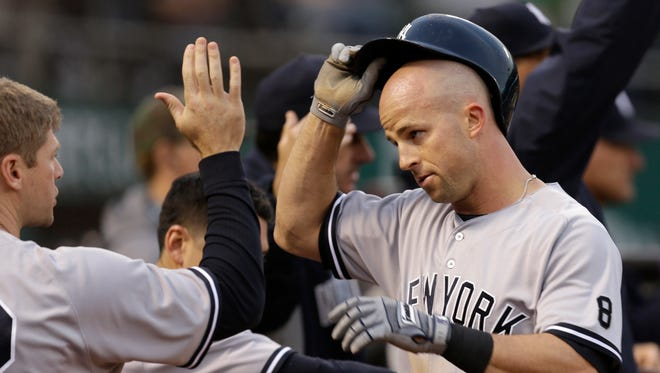 New York Yankees' Brett Gardner, right, is congratulated by Chase Headley after scoring against the Oakland Athletics during the third inning of a baseball game Thursday, May 19, 2016, in Oakland, Calif.