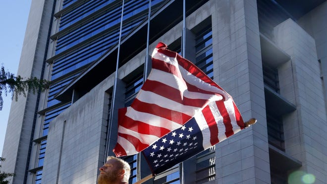 FILE - In this Sept. 13, 2016, file photo, a protestor, who would only identify himself as Robert, flies an upside down United States flag outside the federal courthouse in Portland, Ore., during the trial for the Bundy brothers and five others. It has been a month since jury selection began in the trial of the brothers and five others charged in connection with the winter takeover of the national wildlife refuge in southeast Oregon. (AP Photo/Don Ryan, file)