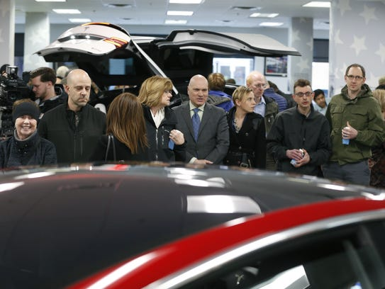 Visitors wait to see the Tesla Models 3,  X and S at