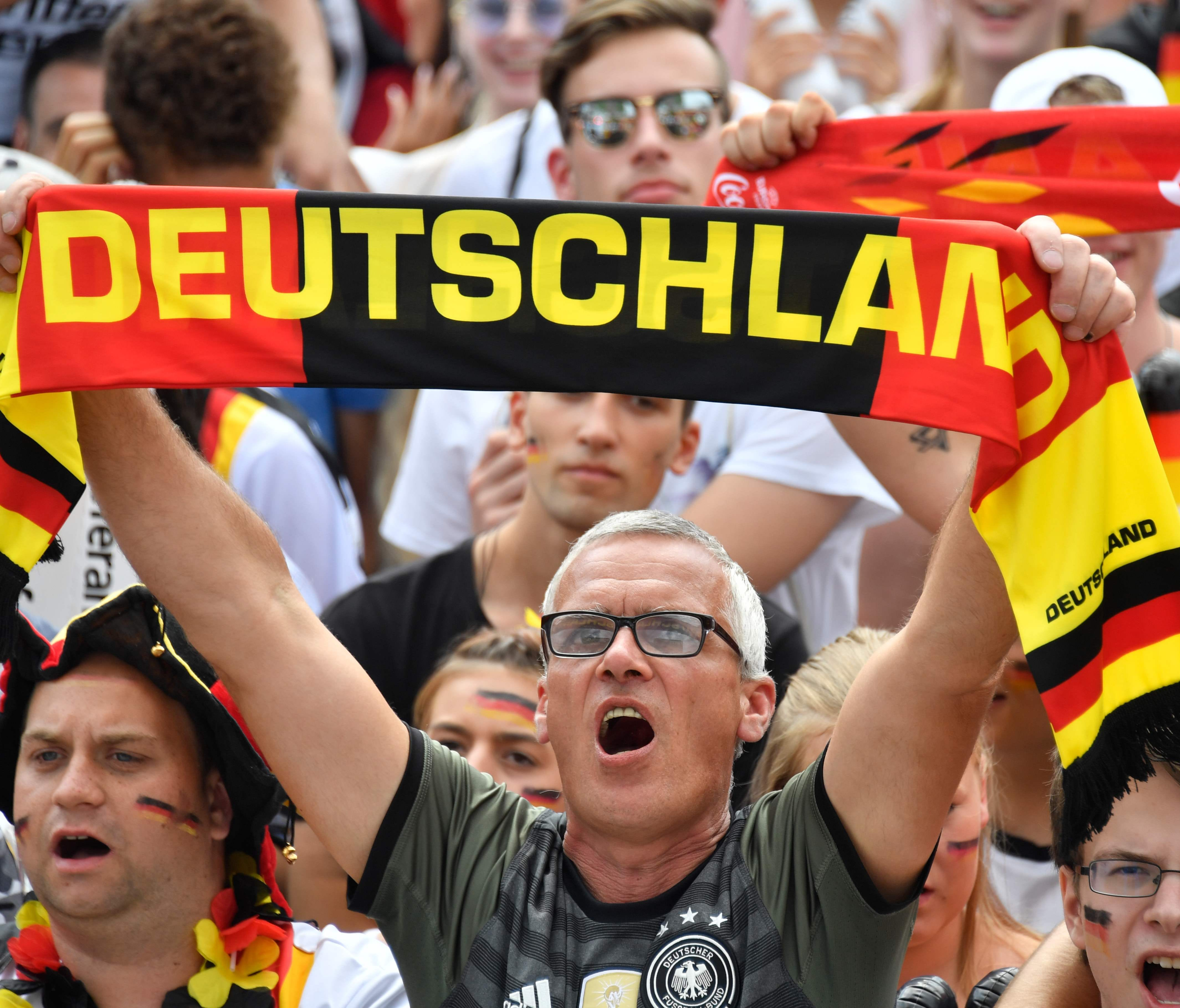 Supporters of the German national soccer team sing the national anthem as they attend a public event in Berlin to watch the World Cup match between South Korea and Germany on June 27, 2018.